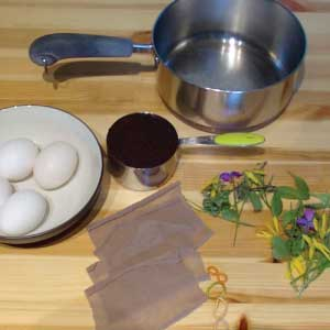 Materials to make coffee dyed eggs--sauce pan, coffee grounds, eggs, nylon squares, rubber bands, flowers, grasses