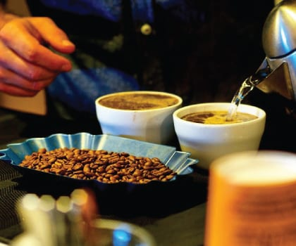 coffee cupping with freshly ground coffee beans and hot water from a kettle